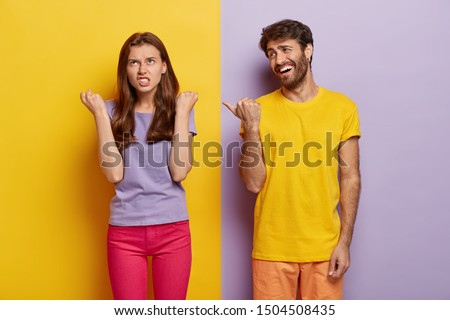 Pleased guy has fun, wears bright yellow t shirt, points thumb at irritated girlfriend who clenches fists with anger, expresses negative emotions, stand in studio against colorful background. Feelings #1504508435