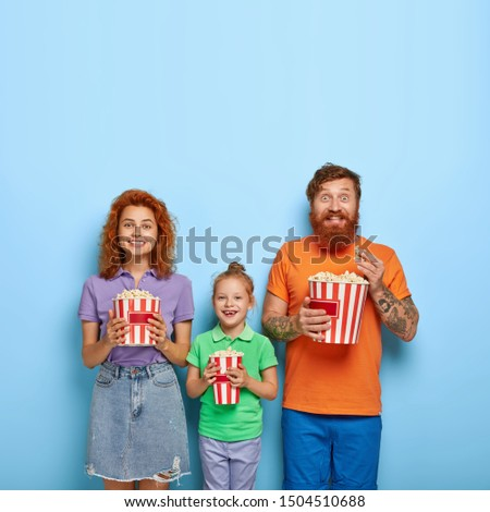Photo of friendly family spend weekend together, watch funny movie, eat popcorn, focused into screen, wear summer clothes, being amused by awesome scene, isolated on blue background, empty space #1504510688