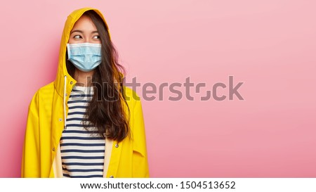 Photo of brunette young ill woman wears protective medical mask, has infectional disease, dressed in yellow raincoat, covers head with hood, looks aside, isolated on pink background, copy space area #1504513652