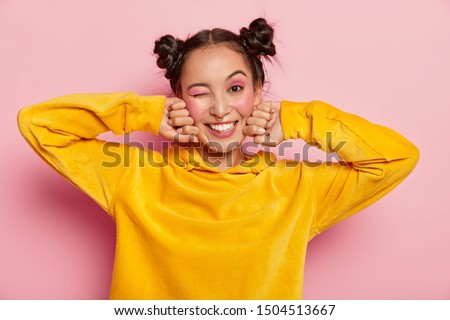 Image of lovely young Asian woman with happy face expression, blinks eye and smiles positively, has fun indoor, two hair knots, dressed in yellow velvet hoody, isolated over pink background. #1504513667