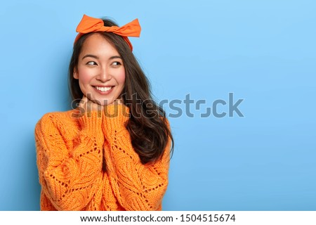 Studio shot of happy upbeat woman wears bright orange knitted jumper, bow headband, holds hands under chin, glad to hear heartwarming words from stranger, rejoices having nice unforgettable day #1504515674