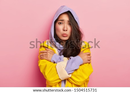 Unhappy young girl feels lonely and cold, looks sadly at camera, keeps hands crossed, wears hoody and raincoat, being dejected by bad weather, gloomy day, expresses negative feelings. Mood, season #1504515731