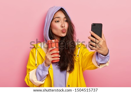 Lovely teenage girl with Asian appearance, keeps lips folded, sends kiss at camera of cellphone, takes selfie, enjoys drink, wears sweatshirt, hood on head, yellow raincoat, has walk after rain #1504515737