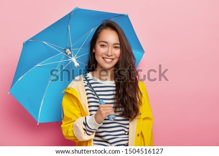 Cheerful brunette Asain woman with long dark hair, wears striped jumper, yellow raincoat, holds blue umbrella, has stroll during rainy day, isolated on pink. Bad weather doesnt spoil my mood #1504516127