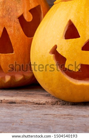 One tooth Jack O Lantern. Cropped image of funny Halloween pumpkin on wooden background. Symbol of traditional autumn holiday.