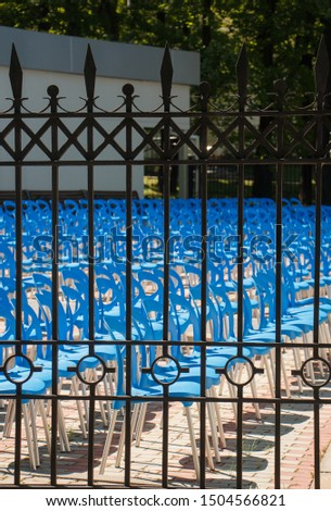chairs chairs stand in a row behind a fence in the Park without spectators #1504566821