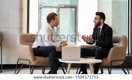 Middle eastern and caucasian ethnicity businessmen seated on armchair in modern office talking solve common issues, banker telling to client regarding bank services make recommendations and consulting #1504571753