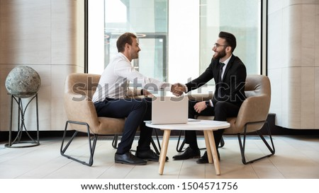 Horizontal view european and arabian businessmen in formal wear accomplish meeting shaking hands feels satisfied after negotiations, HR manager greeting applicant before job interview process concept #1504571756