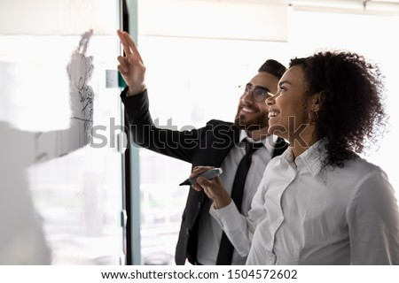 Multiracial entrepreneurs working together on business plan creation, arab and african mates preparing presentation for company clients or investors talking discuss issues share ideas use flip chart