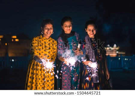 Three young Indian women with bengal fireworks, celebrating Indian Festival Diwali. #1504645721