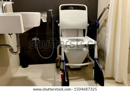 A commode chair or mobile toilet seat placed over a toilet bowl in a hospital bathroom where patients with difficulties walking or are disabled can be conveniently wheeled in to ease themselves. #1504687325
