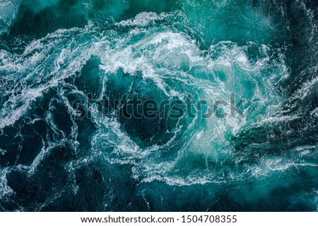 Waves of water of the river and the sea meet each other during high tide and low tide. Whirlpools of the maelstrom of Saltstraumen, Nordland, Norway Royalty-Free Stock Photo #1504708355