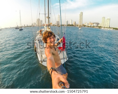 Selfie photo of a sporty guy hanging on the rear of a sailboat while cruising towards the shore. Self picture of young millennial tourist enjoying wanderlust holiday trip in Cartagena City, Colombia.