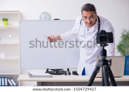 Young male doctor recording video for his blog #1504729427