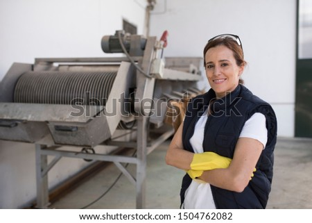 Woman posing near to machine conveyer belt for olives packaging #1504762082
