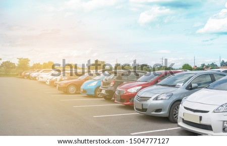 Car parking in large asphalt parking lot with trees, white cloud and blue sky background in sunny day. Outdoor parking lot with fresh ozone and green environment of transportation and technology