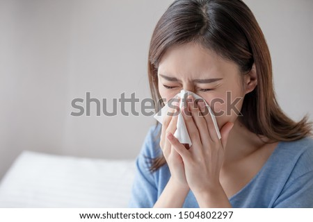 asian woman sick and sneeze with tissue paper in the bedroom #1504802297