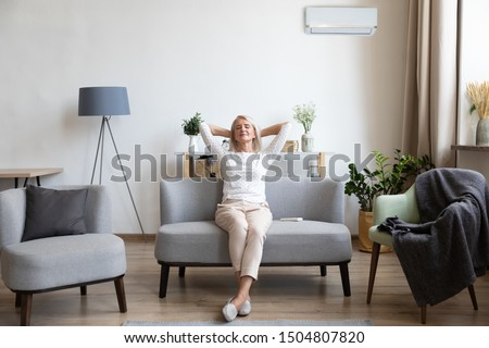 Relaxed satisfied older woman sitting leaning back on couch in air conditioner room, happy peaceful mature female with hands behind head resting on sofa at home, enjoying fresh air, breathing #1504807820