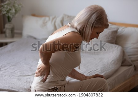 Upset mature woman suffering from backache after sleep, rubbing stiff muscles, unhappy older female sitting on bed at home, feeling discomfort, because of bad posture or uncomfortable bed #1504807832