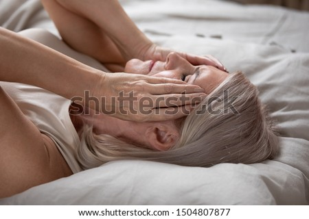 Unhappy exhausted mature woman with closed eyes lying in bed, touching temples close up, tired older female suffering from headache or migraine, feeling unwell, suffering from insomnia, lack of sleep #1504807877