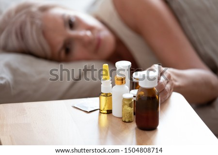 Unhealthy mature woman lying in bed, taking medicine from cold or insomnia, unhappy older female suffering from flu or seasonal fever, treatment concept, pills and meds on bedside table close up Royalty-Free Stock Photo #1504808714