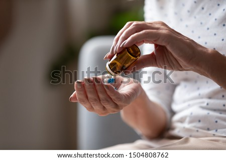 Close up mature woman taking out pills from bottle, supplements or antibiotic, older female preparing to take emergency medicine, chronic disease, healthcare and treatment concept #1504808762