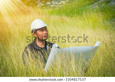 Engineer sitting in the field with blueprint Corporate Achievement Planning, Strategic planning, analysis of new architectural plans, Strategies and engineering risk concept. #1504817537