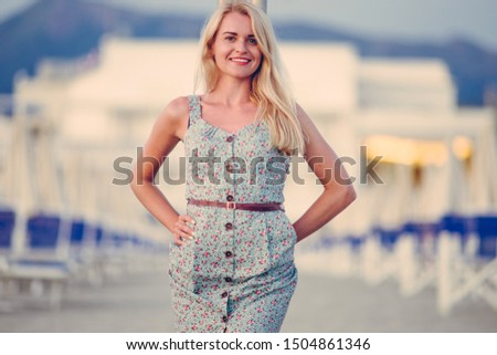Blonde caucasian woman with an elegant fashionable dress and her wooden bag posing in a portrait session near the sea at sunset #1504861346