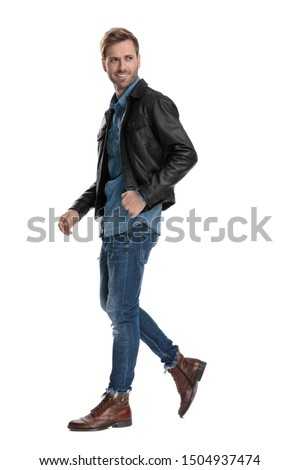 side view of a fine casual man with black leather jacket walking and looking over shoulder happy on white studio background #1504937474