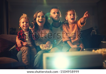 family mother father and children watching projector, TV, movies with popcorn in the evening   at home  #1504958999