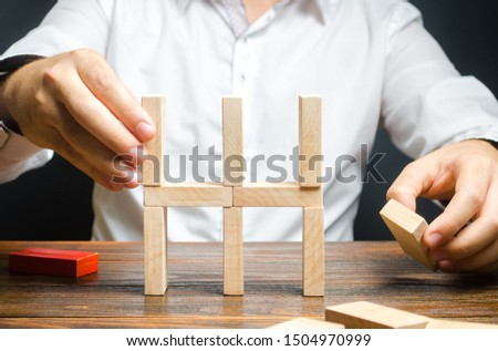 Businessman collects a house of dominoes. Conceptual creation of a new business or startup, establishing processes. Construction of a residential building. Mortgage. Real estate market and investment. #1504970999