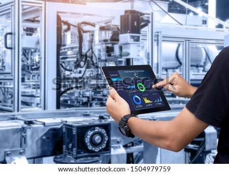 Smart industry control concept.Hands holding tablet on blurred automation machine as background Royalty-Free Stock Photo #1504979759