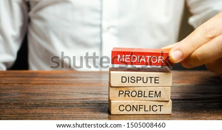A man holds wooden blocks with the word Mediator, dispute, problem, conflict. Settlement of disputes by mediator. Dispute Resolution and Mediation. Third party, intermediary. #1505008460