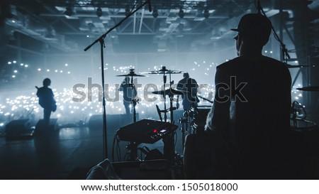 Music band group silhouette perform on a concert stage.   silhouette of drummer playing on drums audience holding cigarette lighters and mobile phones #1505018000