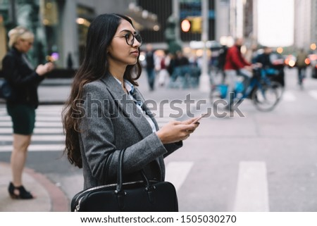Side view of young businesswoman in office wear and glasses using mobile phone while crossing street in New York City  #1505030270