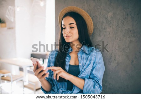 Ukrainian millennial female blogger search fashion publications about last trends connected to 4g wireless on cellphone, Caucasian hipster girl in stylish hat watching video via application on mobile #1505043716