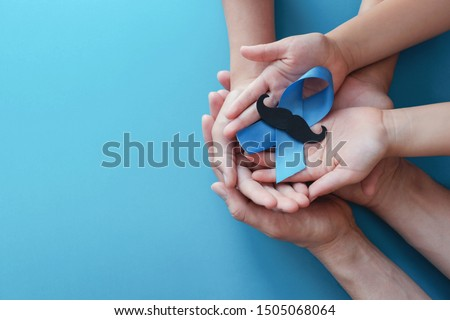 Family hands holding light blue ribbonwith mustache on blue background , Prostate Cancer Awareness, Men health awareness, Movember November Blue #1505068064
