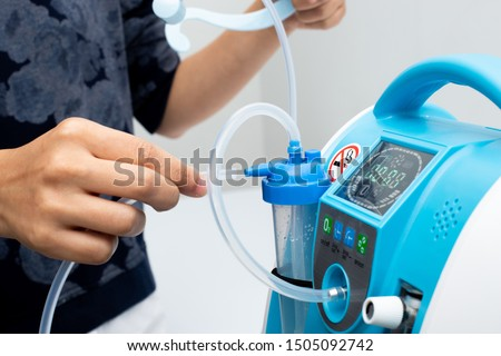 Medical Device Individual Blue White portable oxygen cylinder to put gas for patients with respiratory disorders, woman hand try to plug in the rubber tube to tank #1505092742