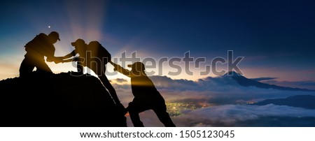 Young asian three hikers climbing up on the peak of mountain near mountain fuji. People helping each other hike up a mountain at sunrise. Giving a helping hand. Climbing. Helps and team work concept Royalty-Free Stock Photo #1505123045