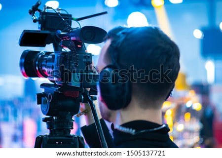Video operator. Videography.Filming.A man is shooting a video.The work of a videographer. Shooting with a professional camera with a tripod. A man shoots on a professional video camera.Videographer #1505137721