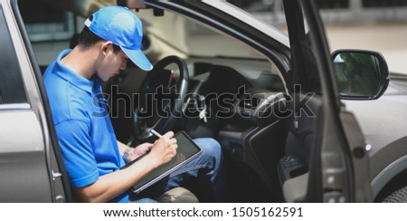 Young delivery man checking the products to customer with tablet while sitting on the car #1505162591