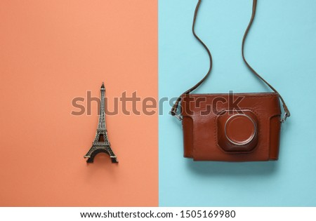 Retro picture with retro camera and eiffel tower figure on colored paper background. #1505169980