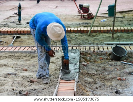 Constructor worker is levelling concrete at construction site/labor #1505193875