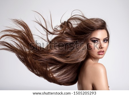 Portrait of a beautiful woman with a long hair. Young  brunette model with  beautiful hair - isolated on white background. Young girl with hair flying in the wind. #1505205293