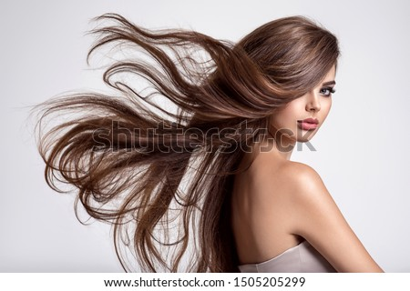 Portrait of a beautiful woman with a long hair. Young  brunette model with  beautiful hair - isolated on white background. Young girl with hair flying in the wind. #1505205299