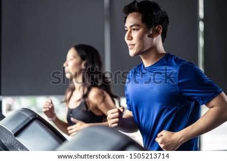 Young fit handsome Asian man and beautiful Asian woman running on treadmill or running machine in modern fitness gym. Seen from side view while they focusing on running. Workout in Gym and fitness. #1505213714
