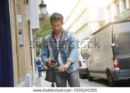 Modern man scanning electric scooter for ride #1505241305