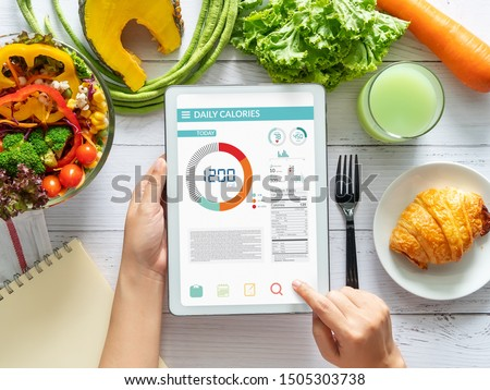 Calories counting , diet , food control and weight loss concept. woman using Calorie counter application on tablet at dining table with fresh vegetable salad #1505303738