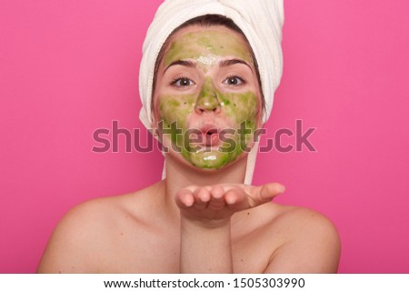 Beauty portrait of relaxed Caucasian woman in spa salon with green facial mask, wearing white towel isolated over rose background, charming female showing kiss gesture, looking directly at camera. #1505303990