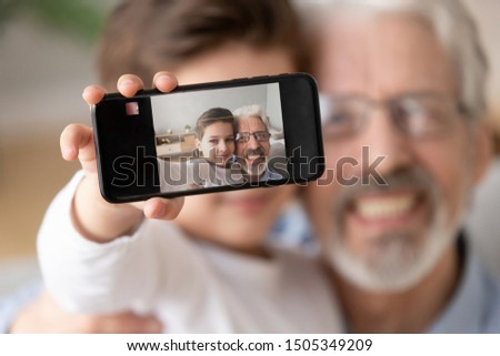 Cute little boy grandson embrace happy old grandfather hold phone take selfie, two generation family small grandchild and senior grandparent bonding make photo self portrait, focus on mobile display
